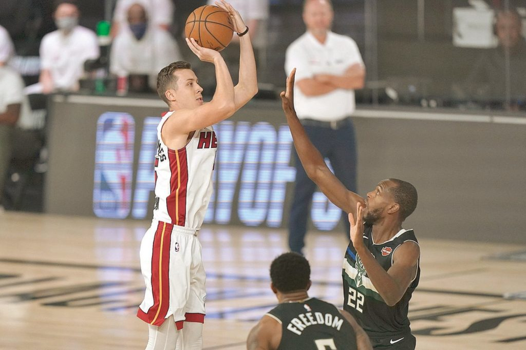 Miami Heat's Duncan Robinson (55), left, shoots over Milwaukee Bucks' Khris Middleton (22) during the first half an NBA conference semifinal playoff basketball game Wednesday, Sept. 2, 2020, in Lake Buena Vista, Fla. (AP Photo/Mark J. Terrill)